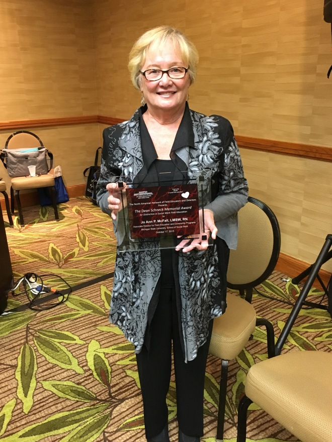 Jo Ann holding the Dean Schneck Memorial Award at CSWE.